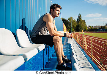 Young handsome male athlete resting after workout and...