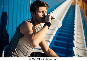 Young handsome male athlete drinking water after workout at...