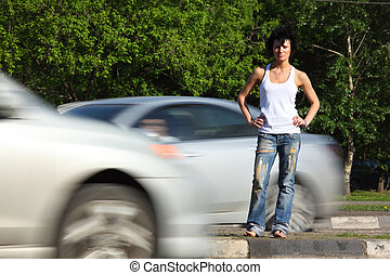 girl stands on road among cars