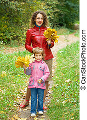 little girl and young woman with maple leaves in hands in park in autumn