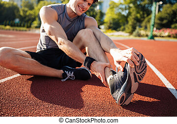 Cropped image of a runner suffering from leg cramp at the...
