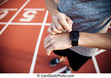 Cropped image of a young muscular man adjusting smart watch...