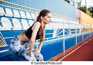 Young beautiful sportswoman leaning on the railing on the...