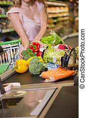 woman buying food at the grocery store - Young woman buying...