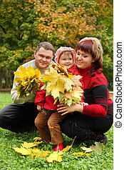 Married couple and little girl collect maple leaves In park in autumn