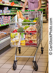 Woman shopping with her trolley full of products