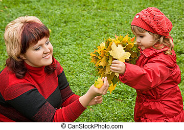 woman and  little girl collect maple leafs In park in autumn