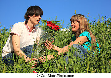 guy gives to girl bouquet of roses among grass