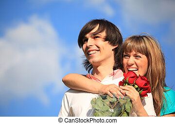girl with bouquet of roses embraces behind guy against sky