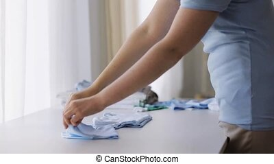 pregnant woman folding baby boys clothes at home 16 -...
