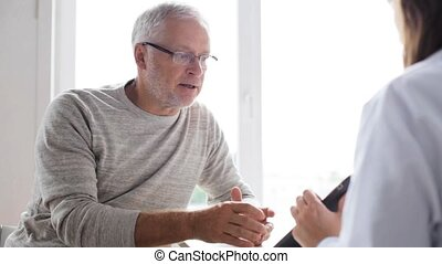 senior man and doctor with tablet pc at hospital 50 -...