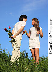 young pair stands on a grass,  guy holds behind back bouquet of roses