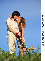 girl with bouquet of roses kisses guy on grass against sky