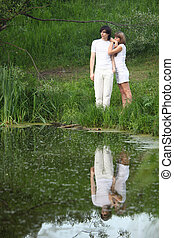 young pair stands on bank of pond