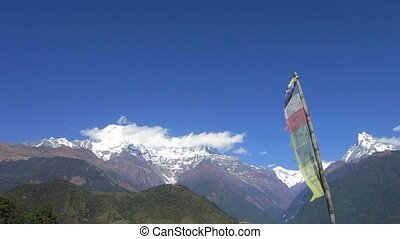 The Annapurna range in Nepal. Prayer flags in the...