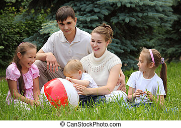 family of five outdoor in summer sit on grass with ball