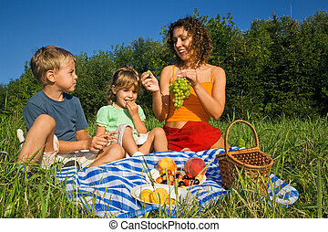 pretty Little Girl and Young Women and Little Boy on picnic in garden