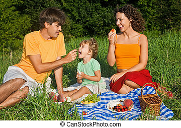 happy family of three on picnic in garden