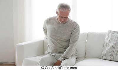 unhappy senior man suffering from backache at home 133 -...