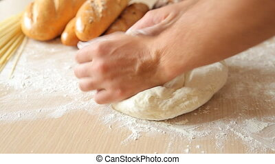 Man hands kneading dough in flour on table. - Man hands...
