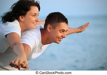 Smiling man and young woman placed hands in sides against sea