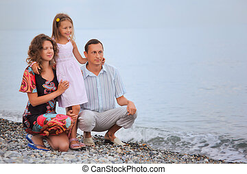 Happy family with little girl on stony beach