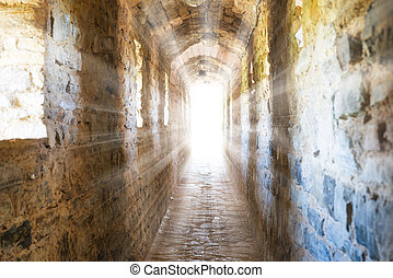 Dark corridor in dungeon with sun rays of light in the end