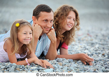 Happy family with little girl lying on stony beach