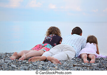 Happy family with little girl lying on stony beach, lying...