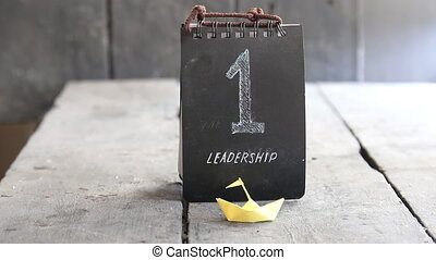 LEADERSHIP text, business concept, paper ship and the number...