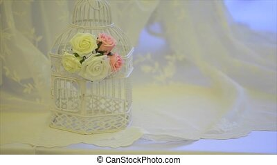 Vintage bird cage decorated with wreath made of pink...