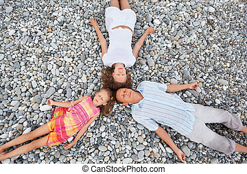 Happy family with little girl lying on stony beach, closed eyes, Concerning with heads
