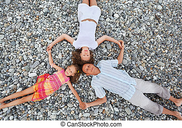 Happy family with little girl lying on stony beach, having...