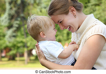 Mother hold baby on hands outdoor in summer and looks on...