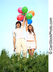 girl and guy stand in grass with multicoloured balloons over...