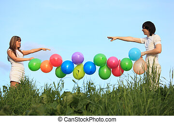 girl and guy hold garland of multicoloured balloons in grass against sky