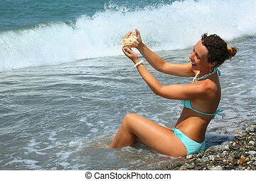 beautiful woman washes seashell in sea