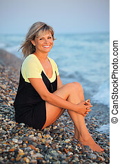 sitting smiling beautiful woman on stone seacoast - sitting...