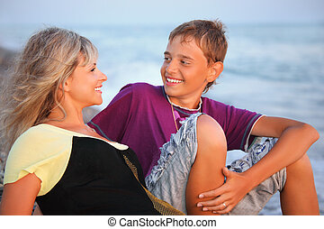 smiling boy and young woman on beach in evening, Looking...