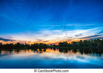 Beautiful colorful sunset on a lake with forest on the other...