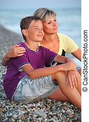 young woman embraces smiling boy on beach in evening,...
