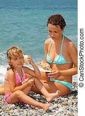 beautiful woman with pretty little girl has leant seashell...