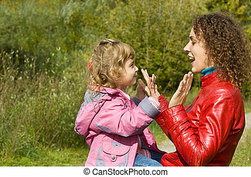 young woman and little girl playing in okie dokey in garden