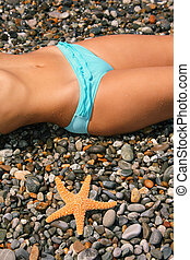 Female beautiful body with on stony beach