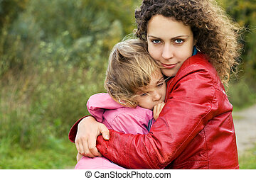 young woman protects little girl from wind in garden