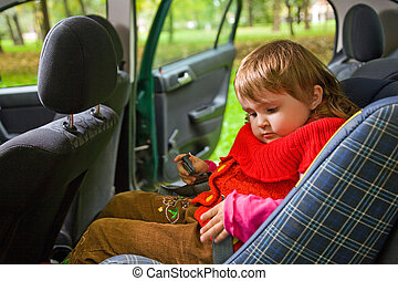 little girl sit in car in park