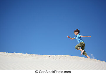 boy runs on sand