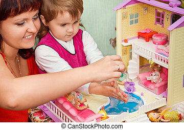 Little Girl and woman washes a doll in pool of toy house