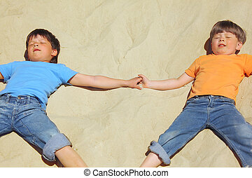 two boys lie on sand with closed eyes