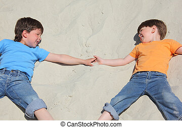 Two children lying nearby on sand look on each other